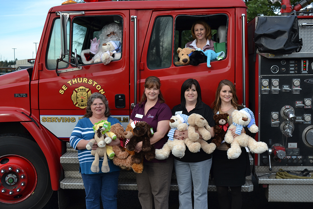 S.E. Thurston Fire Authority receives a generous donation of teddy bears and stuffed animals from TwinStar Credit Union in Yelm. Pictured Left to Right: (Front Row) Kathie Schleis, Rainier/Yelm Fire Department Auxillary, Carol Sandland, Member Service Representative, Janna Niesen, Member Service Representative, Ashley Brazell, Member Service Representative. (Fire Truck Windows) Santa and Kris Kvinsland, Yelm Branch Manager.