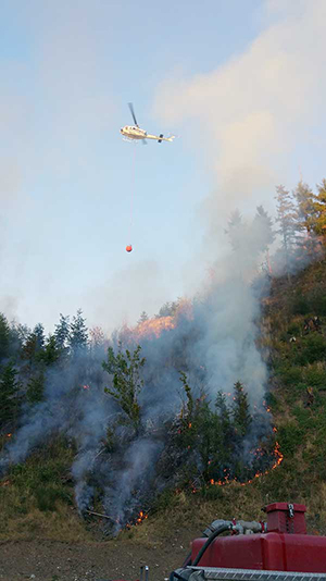 SETFA (Yelm & Rainier Fire Dept.) responds to the Johnson Creek brush fire, July 18, 2015. A DNR helicopter dumps water on fire.
