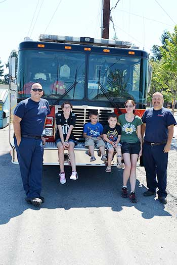 (from left to right): Lieutenant Brian Richardson, Devin Dries, twins Keith and Carson Dries, Miranda Dries, and Firefighter Steve Berg smile in front of a SETFA (Yelm & Rainier Fire Department) fire truck.