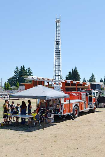 SETFA's (Yelm & Rainier Fire Dept.) booth set up next to fully extended ladder truck.