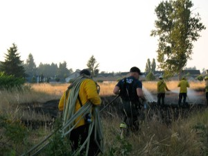 SETFA (Yelm & Rainier) and Department of Natural Resources personnel carry a water hose.