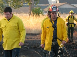 SETFA (Yelm & Rainier) Fire Captain Eric Hetland walks the burnt field with Department of Natural Resources and SETFA personnel.